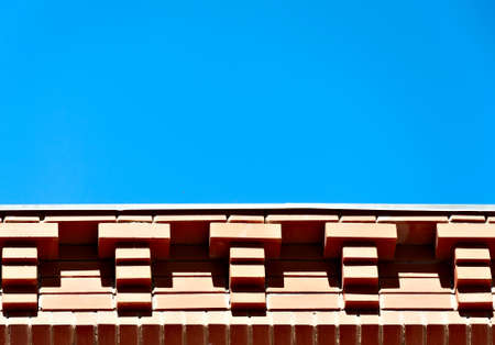 Architectural background - brick eaves against the blue sky. photo