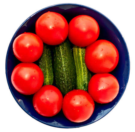 Blue salad bowl with fresh tomatoes and cucumbers, top view. Isolated on white. photo