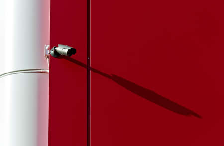 High-tech infrared security camera on the background of a red wall. photo