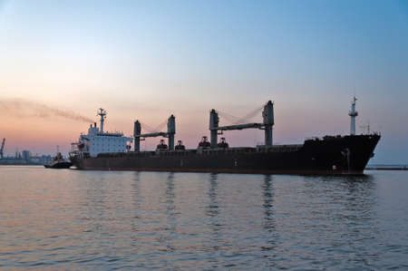 The ore carrier heaves out of the harbor on a tow, the photo is taken at sunset. photo