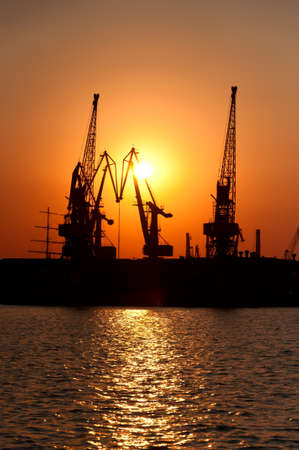Silhouettes of port cranes against a solar disk at sunset. The Odessa seaport, Coasting harbour. Ukraine. photo