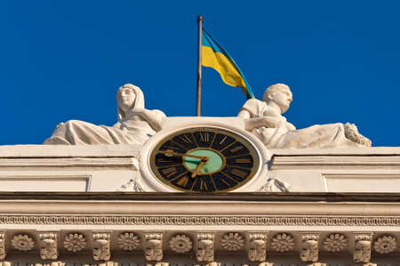 Fragment of a facade of a building of the Odessa city council - chiming clock, sculptural composition and a national flag of Ukraine Stock Photo - 15439559