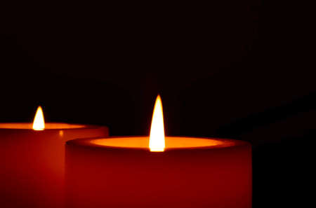 Two big burning candles, close up, on a black background.