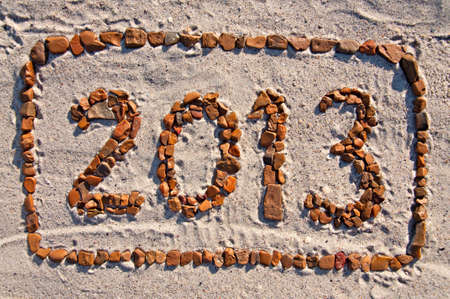 Digits 2013 - numbers in the frame, lined with pebbles on the sand  photo