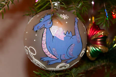 christmas dragon: Christmas ornament - a sphere on a fir-tree with the image of a dragon