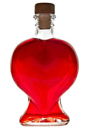赤い液体が白い背景で隔離の心臓の形をしたボトル