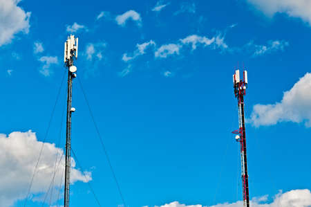 Two cell towers over blue sky background  Horizontal view photo
