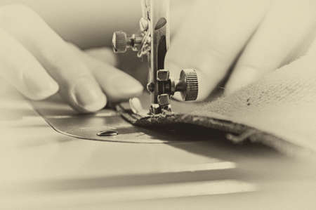 Retro Sewing Process - Women's hands behind her sewing. Closeup photo