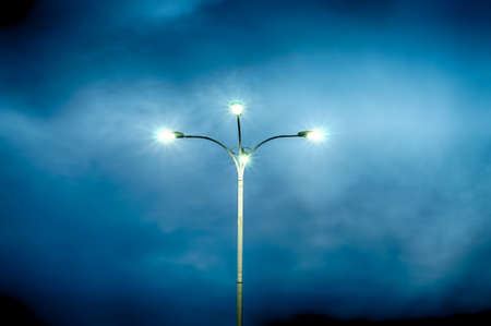 Lamppost with four lamps over background of a dramatic sky. HDR image. 写真素材