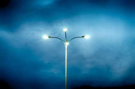 劇的な空の背景の上の 4 つのランプの街灯。HDR 画像。