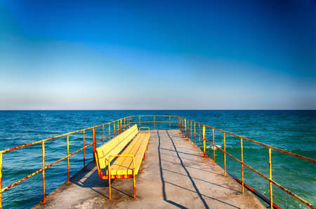 Bench on a pier near the sea in a bright sunny day.  Nobody. HDR image. photo