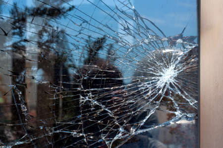 broken house: Broken Glass with outdoor street reflection. Closeup. Stock Photo