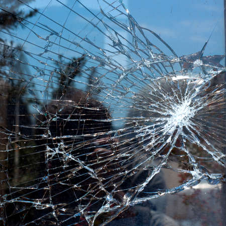 Broken Glass with outdoor street reflection. Closeup. Stock Photo