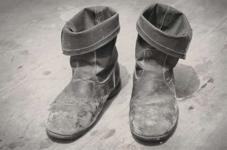 Old Boots - distressed and dirty, on a the same wooden floor. photo