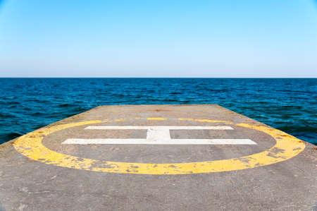 Helipad on a concrete pier near the sea against a clear sky. Closeup. photo