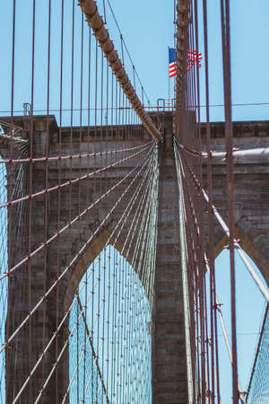 Brooklyn Bridge with stars and stripes banner, New York City, USA