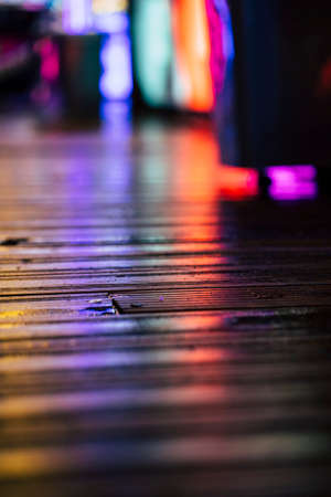 Neon Light Reflections on a wet wooden floor at a midnight fair