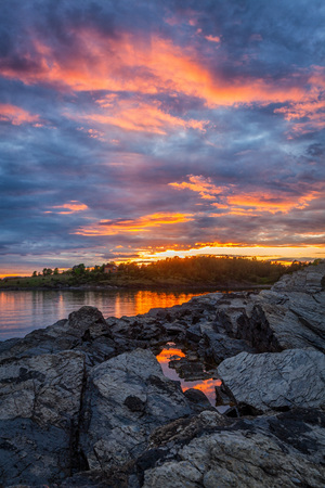e Oslo fjord in majestic colors at sunset time. The rocks in the foreground are forming leading lines towards the sea and the cloud scape. the water reflects the clouds and the colors from the sky.