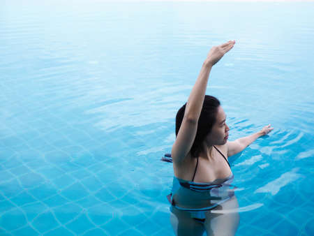 beautiful professional asian woman practice aqua yoga water therapy side bend twist pose balance in swimming pool body mind spirit spiritual healing