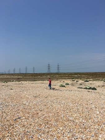 torres de alta tension: Hombre caminando por otro lado Dungeness desierto con Torres de alta tensión en el fondo