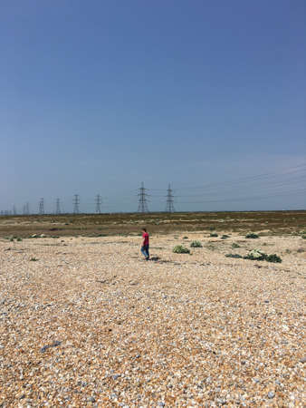 dungeness: Man walking along across Dungeness desert with Pylons in background Stock Photo