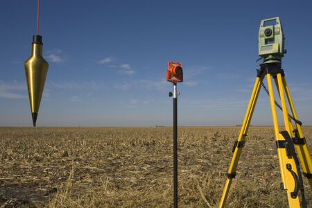Total station, prism and plumb-bob in the field. Stock Photo