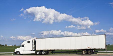camion: Blanco semi-cami�n contra el campo verde y cielo nublado.