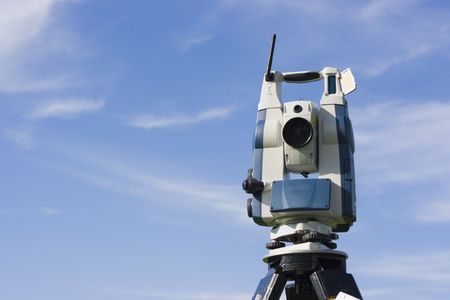 Theodolite against blue sky. photo