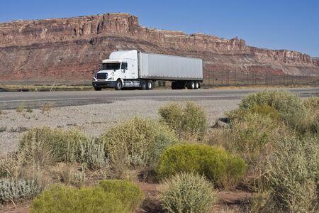 Semi driving dry Utah - Moab area. photo