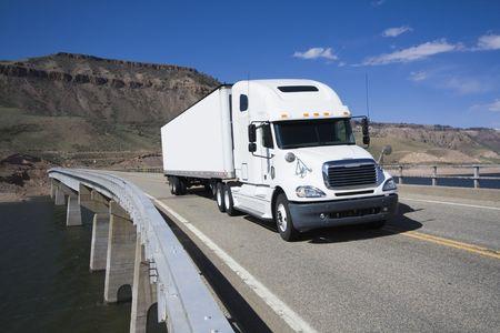 truck driver: White Semi driving the bridge in Colorado. Stock Photo