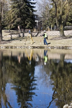 Land Surveyor and his instrument reflected in the pond.