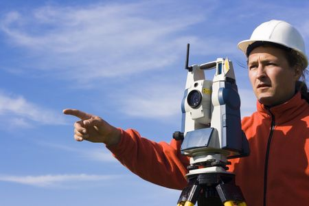 surveyor: Land Surveyor in the field - spring surveying. Stock Photo