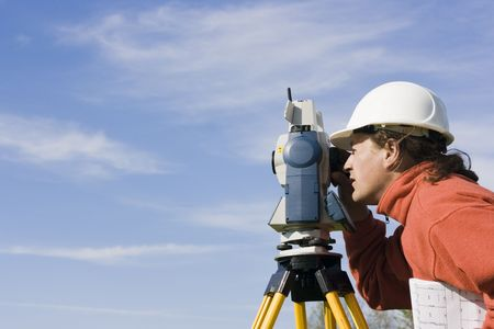 cartographer: Measuring with theodolite - spring land surveying. Stock Photo
