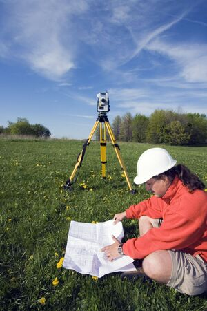 Analizing a map - spring land surveying. Stock Photo
