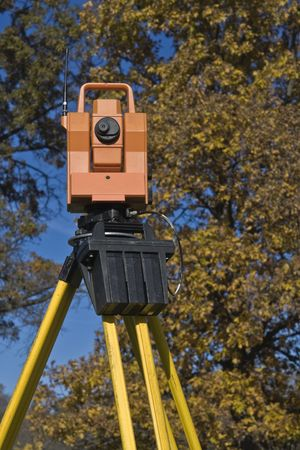 land surveying: Theodolite against a tree - fall land surveying.