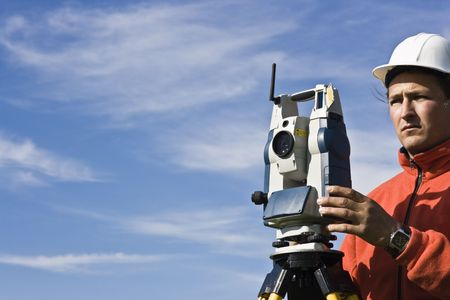 topography: Behind Theodolite - spring land surveying.