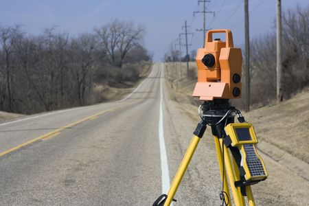 topography: Theodolite set on the edge of road - spring land surveying. Stock Photo
