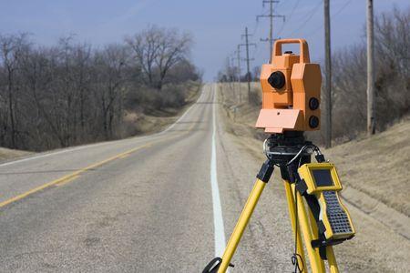 Theodolite set on the edge of road - spring land surveying. Фото со стока