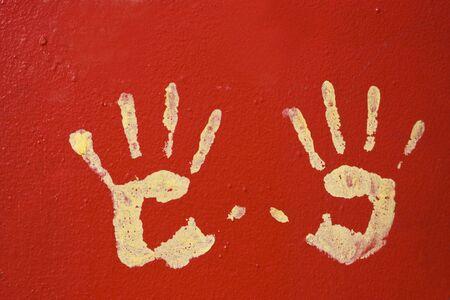 Jaune mains sur le rouge, le mur de métal. Banque d'images - 5834793