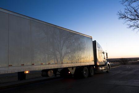 White Semi Truck seen at sunrise photo