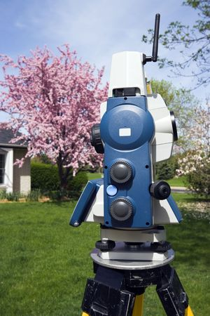 Theodolite and spring colors on trees.
