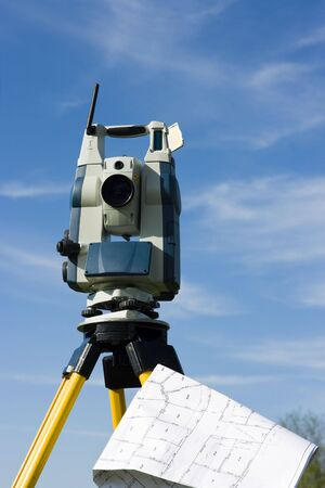 Theodolite and a map with shown subarban properties. photo