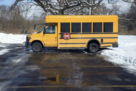 Small school bus on the parking lot - winter time.