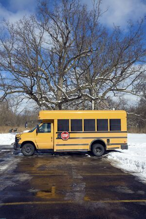 Small school bus on the parking lot - winter time. photo