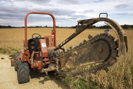 trencher: Old style trenching machine in the field. Stock Photo