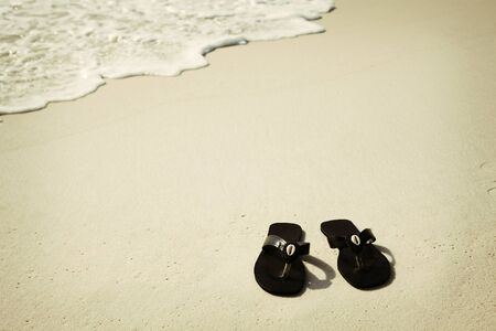 Black flip flops with shells on the beach photo