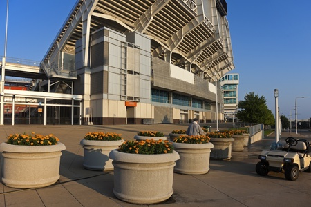 Man taking care of flowers in front of the Cleveland Browns stadium
