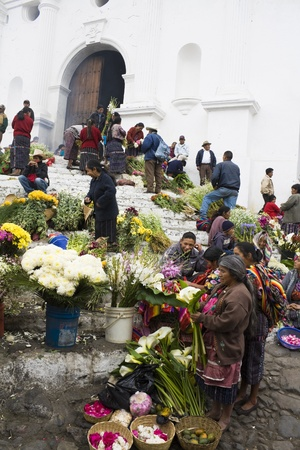 Chichicastenango, Guatemala - February 01, 2009: Sunday market in Chichicastenango. Women selling flowers on the stairs of the church.