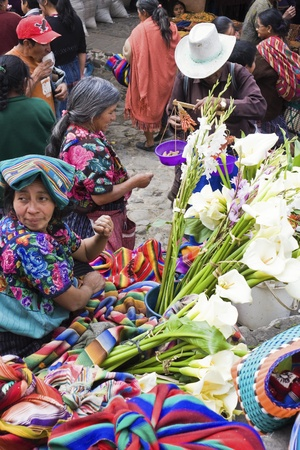 01: Chichicastenango, Guatemala - February 01, 2009: Sunday market in Chichicastenango. Women selling flowers on the stairs of the church.