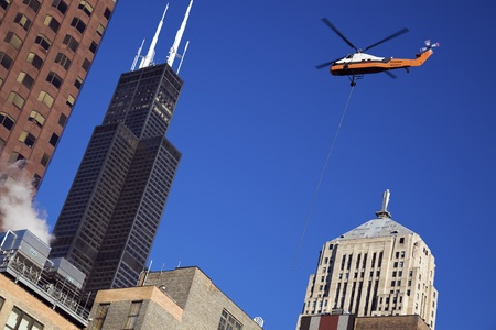 sears: Chicago, Illinois, USA - October 10, 2010: Construction work in downtown Chicago - helicopter in use. Willis Tower (Sears Tower) on the left. Seen Saturday morning.